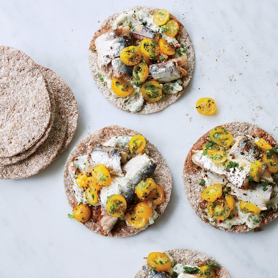 """<p>This recipe from Food & Wine's Justin Chapple makes the most of canned sardines. Chapple prepares a bright herb mayo to spread on rye crisps, then tops them with a cherry tomato salad and good-quality sardines. The juices from the tomatoes soften the rye crisps ever so slightly.</p><p><a href=""""https://www.foodandwine.com/recipes/rye-crisps-tomatoes-and-sardines"""">GO TO RECIPE</a></p>"""