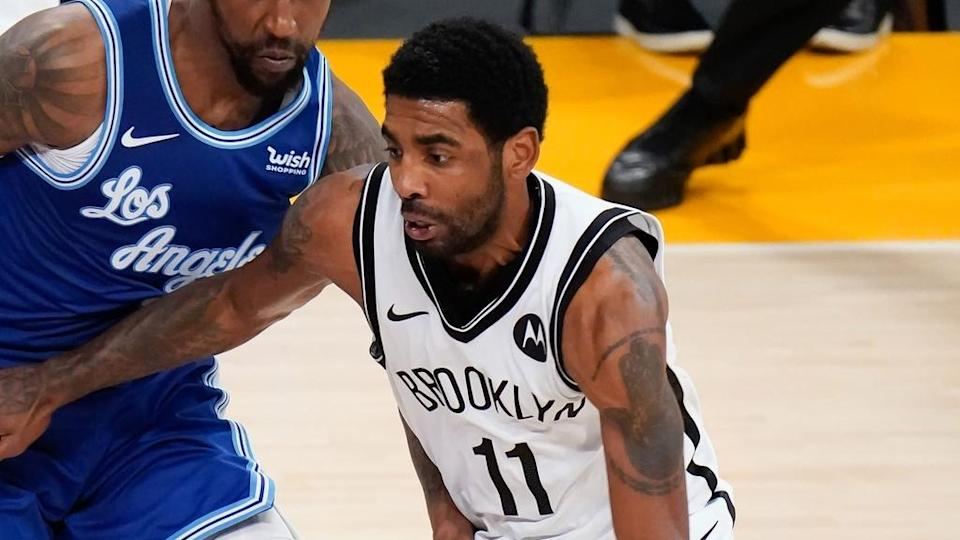 Kyrie Irving dribbles past Lakers defender in white jersey tight shot