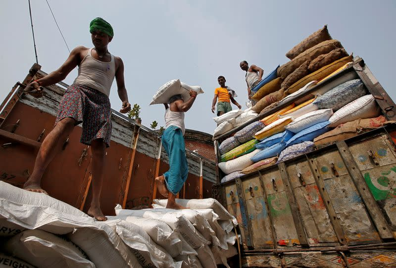 FILE PHOTO: A labourer carries a sack filled with sugar to load it onto a supply truck at a wholesale market in Kolkata