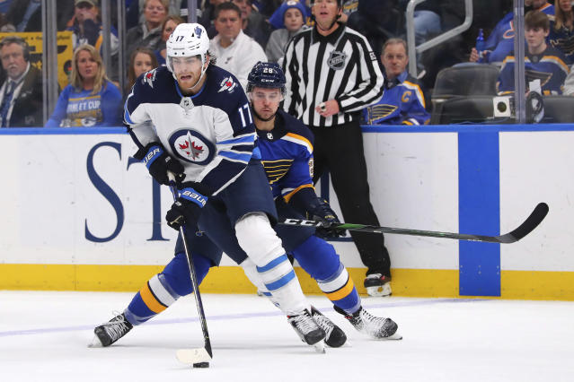 Winnipeg Jets center Adam Lowry (17) controls the puck against St. Louis Blues winger Mackenzie MacEachern (28) during the third period of an NHL hockey game Sunday, Dec. 29, 2019, in St. Louis. (AP Photo/Dilip Vishwanat)