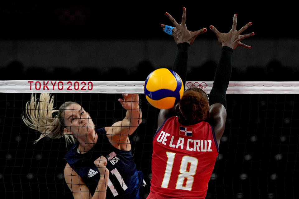 United States' Andrea Drews, left, spikes the ball past Dominican Republic's Bethania de la Cruz de Pena during the women's volleyball quarterfinal match between Dominican Republic and United States at the 2020 Summer Olympics, Wednesday, Aug. 4, 2021, in Tokyo, Japan. (AP Photo/Frank Augstein)