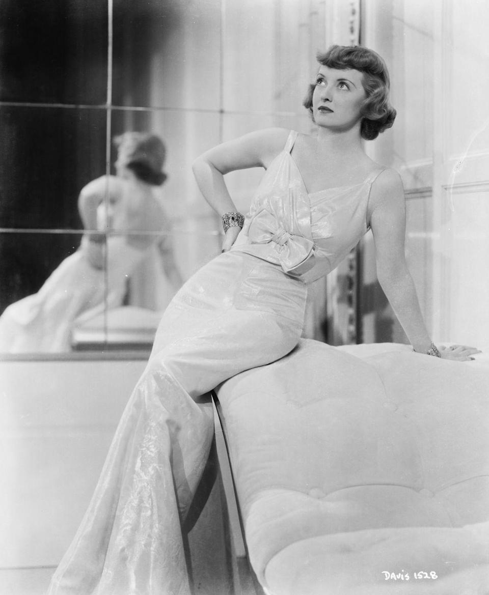 <p>In another portrait for Warner Bros., Davis wears a ballgown in front of a mirrored wall.</p>
