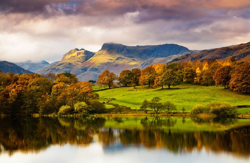 A picturesque scene of the Lake District in Autumn with a reflective lake, imposing peaks, and moody clouds - Credit: Anna Stowe Landscapes UK/Alamy