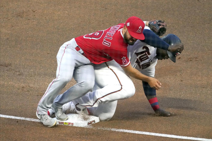 Minnesota Twins' Miguel Sano, right, collides with Los Angeles Angels third baseman Jack Mayfield as Sano stole third base during the fourth inning of a baseball game Thursday, July 22, 2021, in Minneapolis. (AP Photo/Jim Mone)