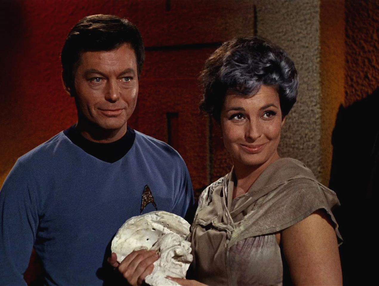 American actor DeForest Kelley (1920 - 1999) as Dr. Leonard 'Bones' McCoy and American actress Jeanne Bal (1928 - 1996) as Nancy Crater appear in a scene from 'The Man Trap,' the premiere episode of 'Star Trek,' which aired on September 8, 1966. (Photo by CBS Photo Archive/Getty Images)