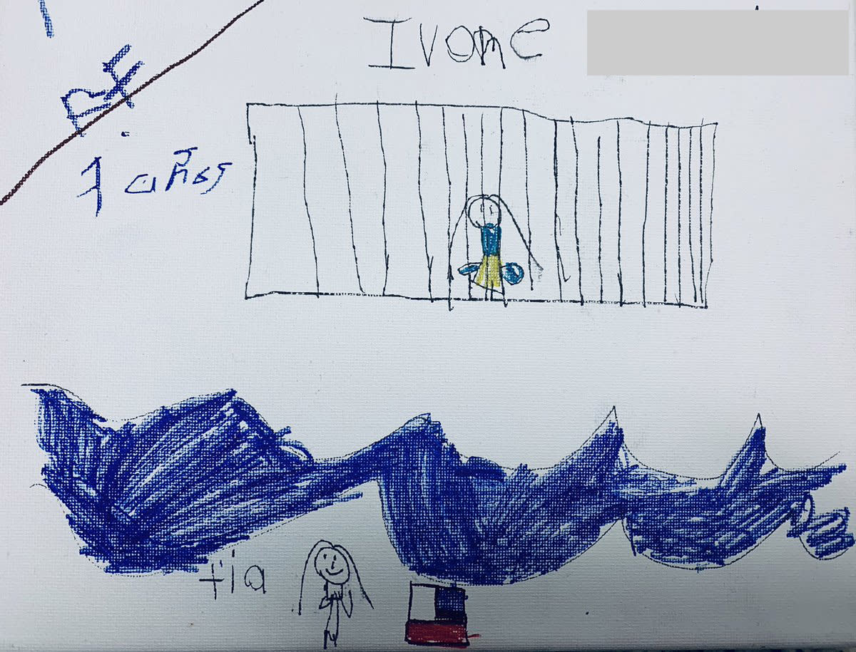 Ivone, 7, draws herself in a cage while her tía watches across the Rio Grande river next to an American flag. | Courtesy of Belinda Arriaga
