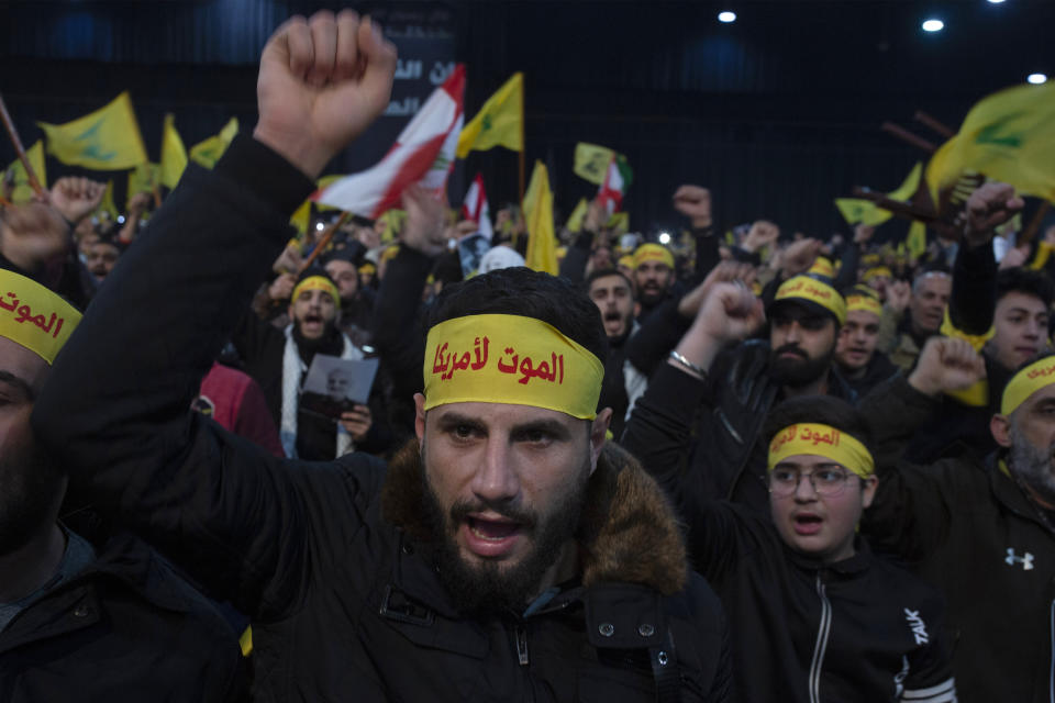"""FILE - In this Jan. 5, 2020 file photo, supporters of Hezbollah leader Sayyed Hassan Nasrallah chant slogans ahead of the leader's televised speech in a southern suburb of Beirut, Lebanon. The headbands read, """"Death to America."""" Twenty years after Hezbollah guerrillas pushed Israel's last troops from southern Lebanon, both sides are gearing up for a war that neither seems to want. Israeli troops are drilling for a possible invasion of Lebanon and striking Hezbollah targets in neighboring Syria. Hezbollah is beefing up its own forces and threatening to invade Israel. (AP Photo/Maya Alleruzzo, File)"""