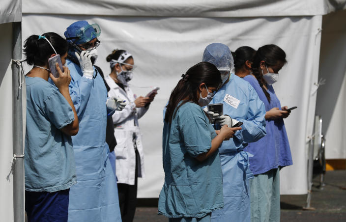 Health workers check their cell phones after an earthquake, outside the Juarez de Mexico public hospital in Mexico City, Tuesday, June 23, 2020. The earthquake centered near the resort of Huatulco in southern Mexico swayed buildings Tuesday in Mexico City and sent thousands into the streets. (AP Photo/Eduardo Verdugo)