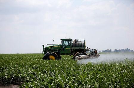 A worker uses a tractor to spray a field of crops during crop-eating armyworm invation at a farm in Settlers, northern province of Limpopo, South Africa, February 8,2017. REUTERS/Siphiwe Sibeko
