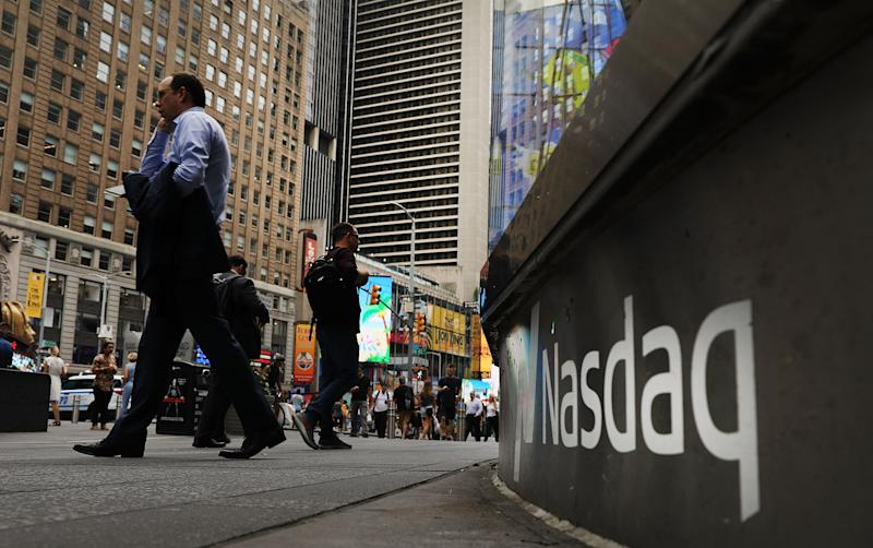 NEW YORK, NY - JULY 30: People walk by the Nasdaq MarketSite in Times Square on July 30, 2018 in New York City. As technology stocks continued their slide on Monday, the Nasdaq Composite dropped 1.1 percent in afternoon trading with shares of Facebook, Netflix, Amazon and Google-parent Alphabet all declining. (Photo by Spencer Platt/Getty Images)