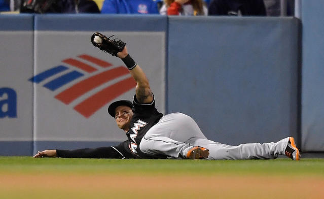 Miami Marlins left fielder Derek Dietrich holds up his glove with the ball after making a catch on a ball hit by Los Angeles Dodgers' Corey Seager during the fifth inning of a baseball game Tuesday, April 24, 2018, in Los Angeles. (AP Photo/Mark J. Terrill)