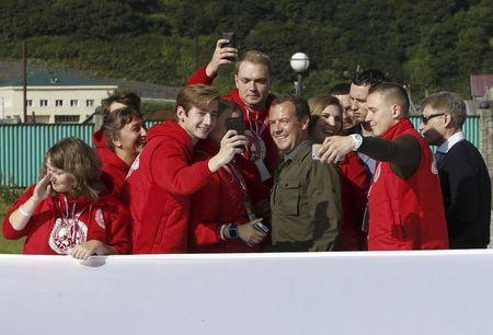 """Russia's Prime Minister Dmitry Medvedev (2nd R, front) poses for a picture with participants of the all-Russian youth educational forum """"Iturup"""" in Kurilsk during his visit to Iturup Island, one of four islands known as the Southern Kurils in Russia and the Northern Territories in Japan, August 22, 2015. REUTERS/Dmitry Astakhov/RIA Novosti/Pool"""