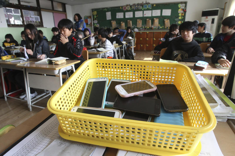 In this Friday, Nov. 9, 2012 photo, smartphones collected from students are placed in a plastic basket during a class at Chilbo elementary school in Suwon, South Korea. Students agreed to hand in their smartphones when they arrive at school in the morning and get them back when they leave for home after classes. Across the entire population, South Korea's government estimated 2.55 million people are addicted to smartphones, using the devices for 8 hours a day or more, in its first survey of smartphone addiction released earlier this year. (AP Photo/Ahn Young-joon)