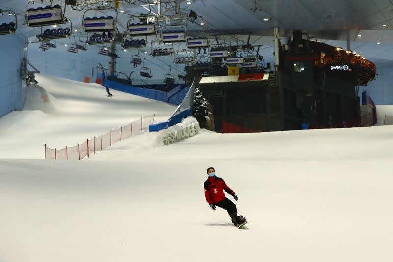 A woman wears a protective face mask as she snowboards at Ski Dubai during the reopening of malls, following the outbreak of the coronavirus disease (COVID-19), at Mall of the Emirates in Dubai