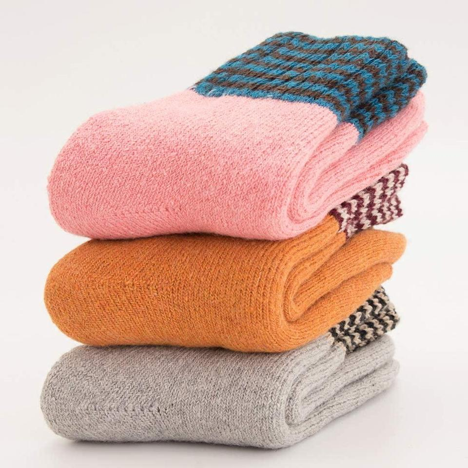 """<h3>Super Thick Wool Socks</h3><br>Split these cute, colorful, wool-and-cotton blend socks up amongst your family members — no need to wrap 'em, just roll and stuff. <br><br><strong>Yoicy</strong> Super Thick Wool Socks (3-Pack), $, available at <a href=""""https://amzn.to/3lmDDm8"""" rel=""""nofollow noopener"""" target=""""_blank"""" data-ylk=""""slk:Amazon"""" class=""""link rapid-noclick-resp"""">Amazon</a>"""