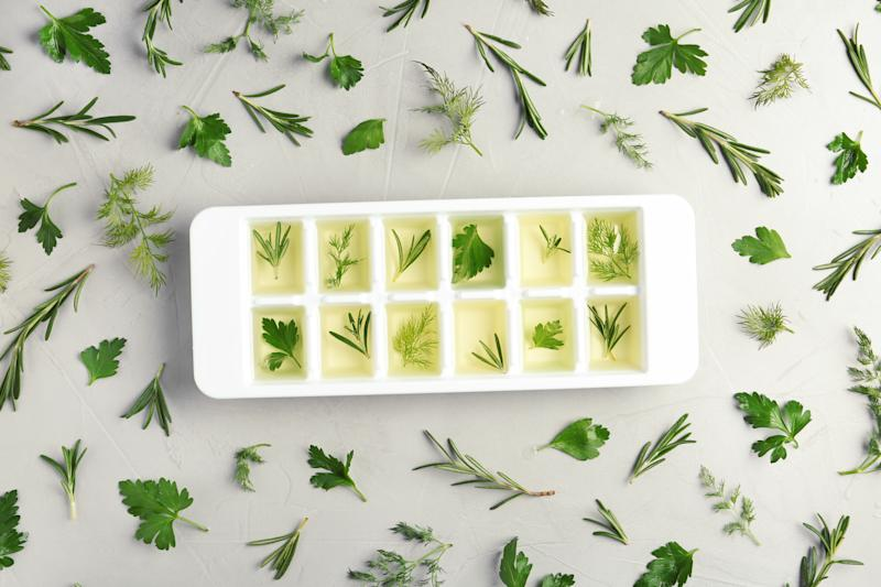 Flat lay composition with ice cube tray and different herbs on grey background