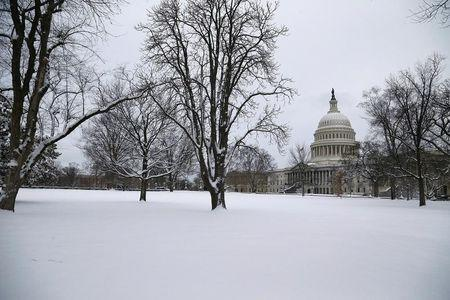 Several inches of fresh snow cover the lawn of the U.S. Capitol in Washington