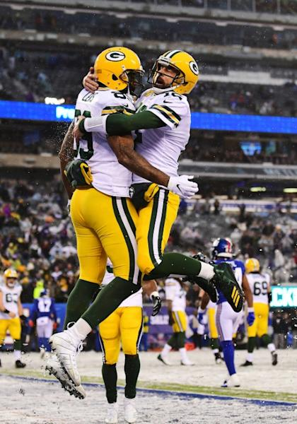 Green Bay quarterback Aaron Rodgers and teammate Marcedes Lewis celebrate a touchdown in the Packers' 31-13 NFL victory over the New York Giants