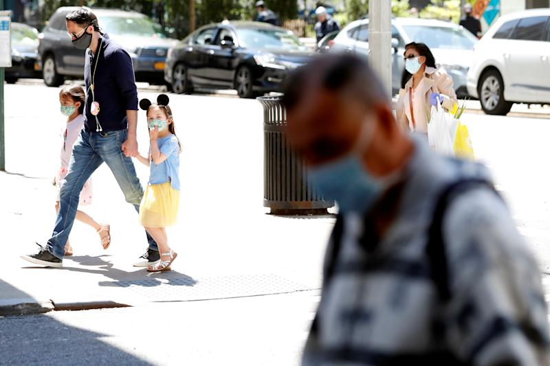 A man holds the hands of two young girls wearing masks as they cross the street as residents of New York City adjust to living with the ongoing outbreak of the coronavirus disease (COVID-19) in the Manhattan borough of New York U.S., May 20, 2020. REUTERS/Lucas Jackson