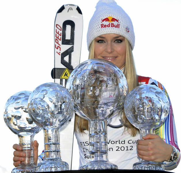 """FILE -This March 18, 2012 file photo shows Lindsey Vonn, of the United States, posing with her alpine ski, women's World Cup trophies for the super-G, super-combined, downhill and overall titles, in Schladming, Austria. The United States ski team says it hasn't had any """"formal discussion"""" yet about the possibility of Lindsey Vonn entering a men's World Cup downhill next month. Vonn, the women's Olympic downhill champion, has written the International Ski Federation to ask whether she can challenge the men on Nov. 24 in Lake Louise, Alberta. Vonn has earned nine of her 26 World Cup downhill victories at the Canadian track, which stages women's races the following weekend. The U.S. Ski and Snowboard Association says """"we clearly have great respect for Lindsey, her accomplishments in the sport and her desire to seek this new challenge. But we have not had any formal discussion yet between Lindsey and FIS."""" FIS secretary general Sarah Lewis tells The Associated Press the governing body can't make a decision on the matter until the team submits a formal request. (AP Photo/Armando Trovati, File)"""