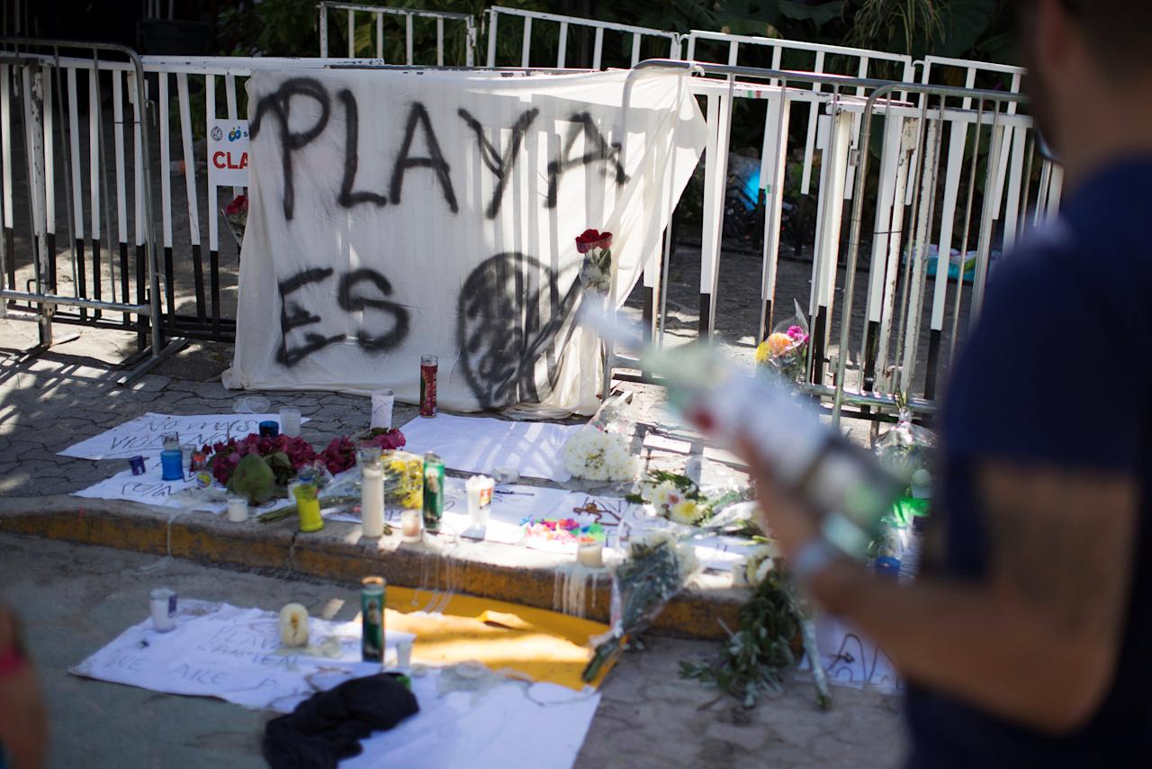 Tourists stand outside the Blue Parrot nightclub where people have left candles and signs in honor of the dead and injured after a gunman opened fire early on Monday, during a BPM electronic music festival, in Playa del Carmen, Mexico January 17, 2017. REUTERS/Victor Ruiz Garcia