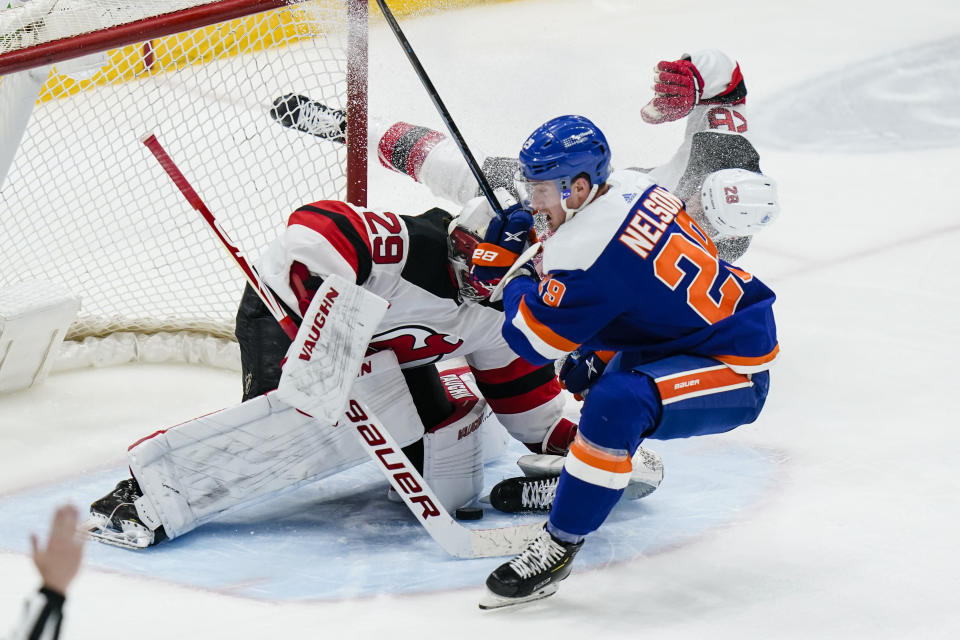 New Jersey Devils goaltender Mackenzie Blackwood (29) stops a shot by New York Islanders' Brock Nelson (29) as Damon Severson (28) defends during the second period of an NHL hockey game Thursday, May 6, 2021, in Uniondale, N.Y. (AP Photo/Frank Franklin II)