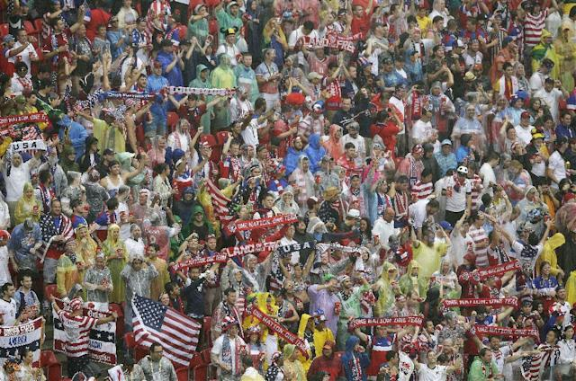 American fans cheer in the rain before the group G World Cup soccer match between the USA and Germany at the Arena Pernambuco in Recife, Brazil, Thursday, June 26, 2014. (AP Photo/Hassan Ammar)