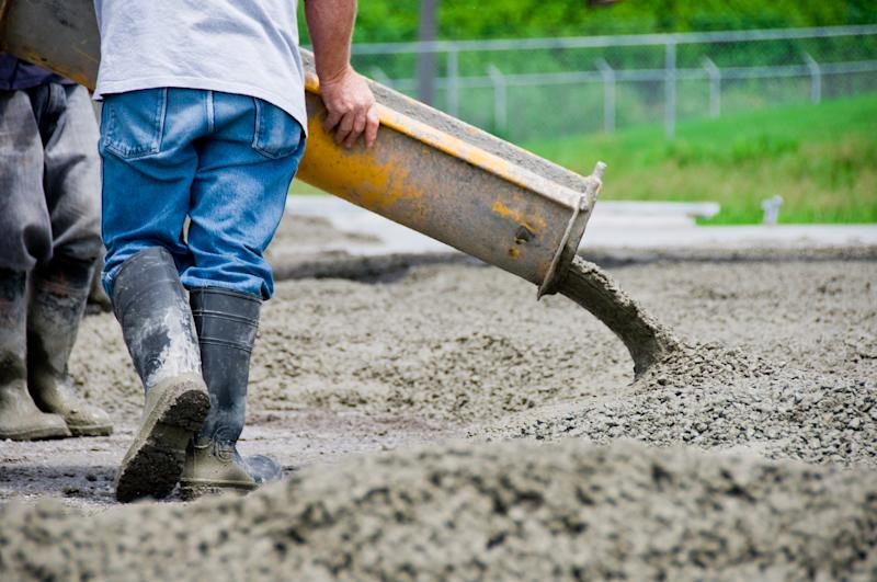 A worker pouring a cement slab.