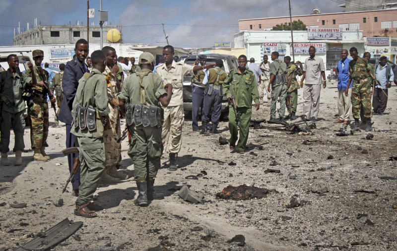 Somali soldiers gather at the scene of a suicide car bomb blast in the capital Mogadishu, Somalia Sunday, May 5, 2013. A Somali police official at the scene said four civilians and a soldier were killed after the suicide bomber attempted to ram a car laden with explosives into a military convoy. (AP Photo/Farah Abdi Warsameh)
