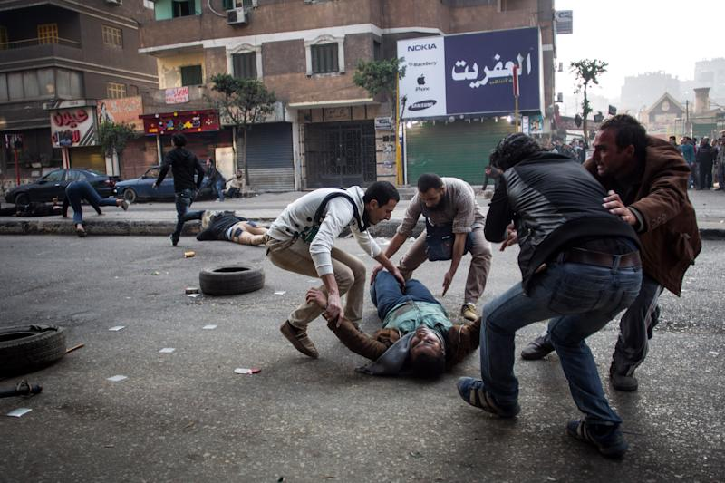 FILE - In this Saturday, Jan. 25, 2014 file photo, a mortally wounded supporter of Egypt's ousted Islamist president is evacuated as another wounded protester lies in the street during clashes with security forces in the Mohandiseen district of Cairo, Egypt. On Tuesday, Feb. 11, 2014, the third anniversary of the day Hosni Mubarak stepped down as Egypt's president after an 18-day uprising, the government blocked access to Tahrir Square and letters emerged from activists reporting that they have been beaten and subjected to other abuses by police after being arrested in a string of protests in late January. (AP Photo/Eman Helal, File)