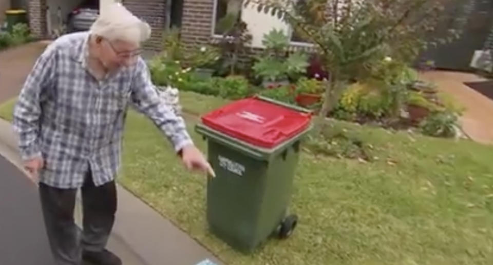 George, a resident of Stockland Retirement Village in Campbelltown, pictured with a bin.