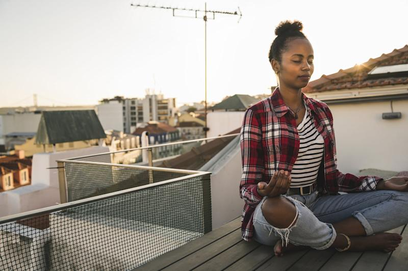 Young woman practicing yoga on rooftop at sunset