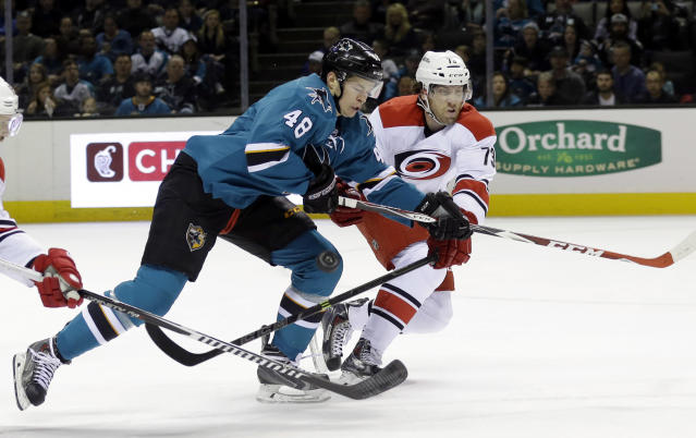 San Jose Sharks' Tomas Hertl (48) fights for possession against Carolina Hurricanes' Brett Bellemore during the first period of an NHL hockey game Saturday, Feb. 7, 2015, in San Jose, Calif. (AP Photo/Marcio Jose Sanchez)