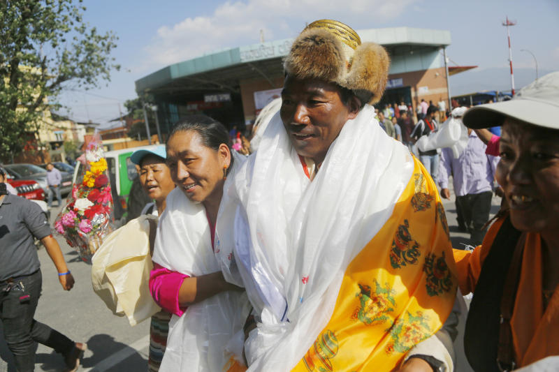 Nepalese veteran Sherpa guide Kami Rita, 49, is welcomed by his wife at the airport in Kathmandu, Nepal, Saturday, May 25, 2019. The Sherpa mountaineer extended his record for successful climbs of Mount Everest with his 24th ascent of the world's highest peak on Tuesday. (AP Photo/Niranjan Shrestha)