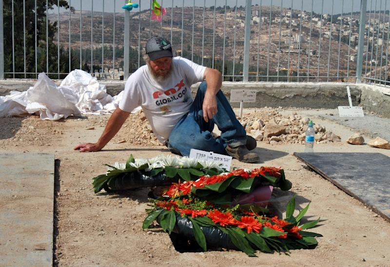 An Israeli mourns next to the newly dug graves of Eitam and Naama Henkin on October 2, 2015 (AFP Photo/Gil Cohen Magen)