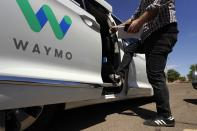 A Waymo minivan arrives to pick up passengers for an autonomous vehicle ride, Wednesday, April 7, 2021, in Mesa, Ariz. Waymo, a unit of Google parent Alphabet Inc., is one of several companies testing driverless vehicles in the U.S. But it's the first offering lifts to the public with no humans at the wheel who can take over in sticky situations. (AP Photo/Ross D. Franklin)
