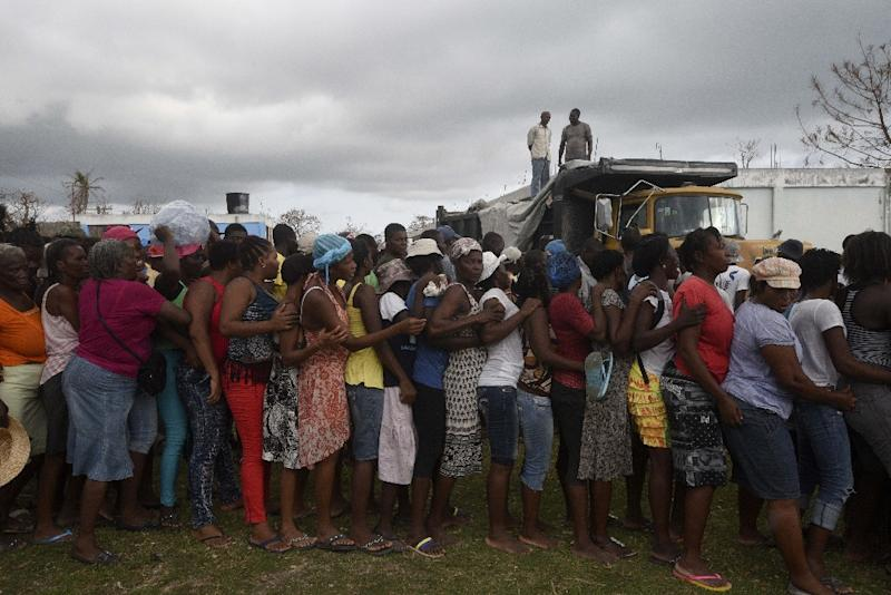People queue for food and clothes being distributed at a shelter in Port-Salut, southwest of Port-au-Prince, on October 9, 2016, days after the passage of Hurricane Matthew through Haiti (AFP Photo/Rodrigo Arangua)