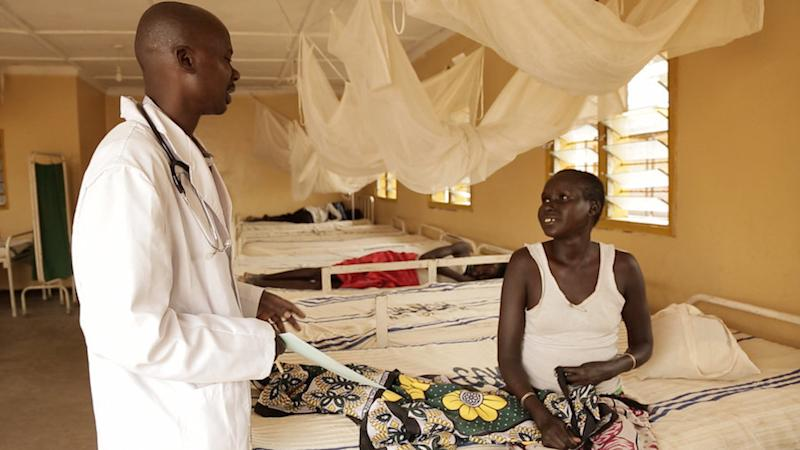 Clinical officer Mark Riongoita speaks with a patient on his rounds in Kacheliba Hospital's specialist kala azar wing in western Kenya. (Zoe Flood)