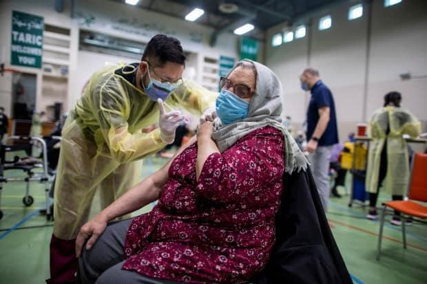 Nurses from Humber River Hospital's mobile vaccine clinic administer the Moderna COVID-19 vaccine at Toronto and Region Islamic Congregation Centre.