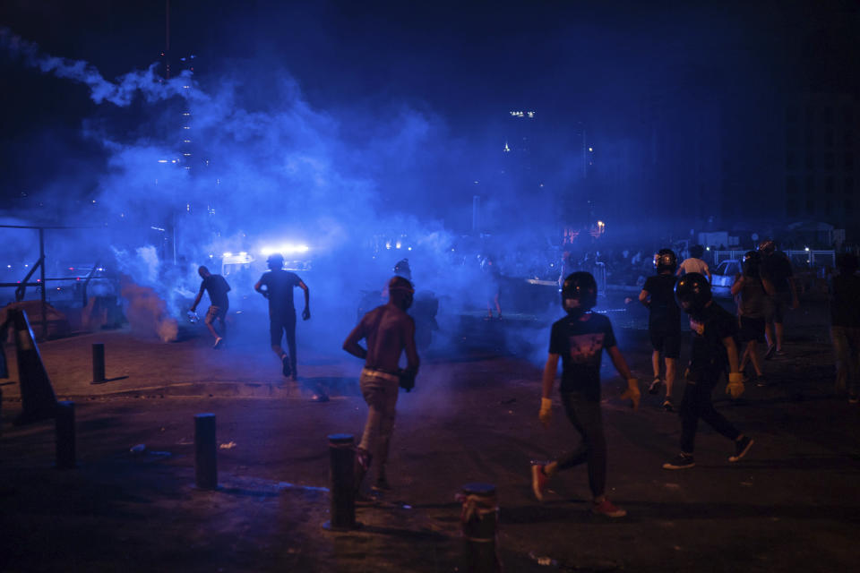 Protesters run from tear gas fired by police forces during an anti-government protest following Tuesday's massive explosion which devastated Beirut, Lebanon, Sunday, Aug. 9. 2020. (AP Photo/Felipe Dana)