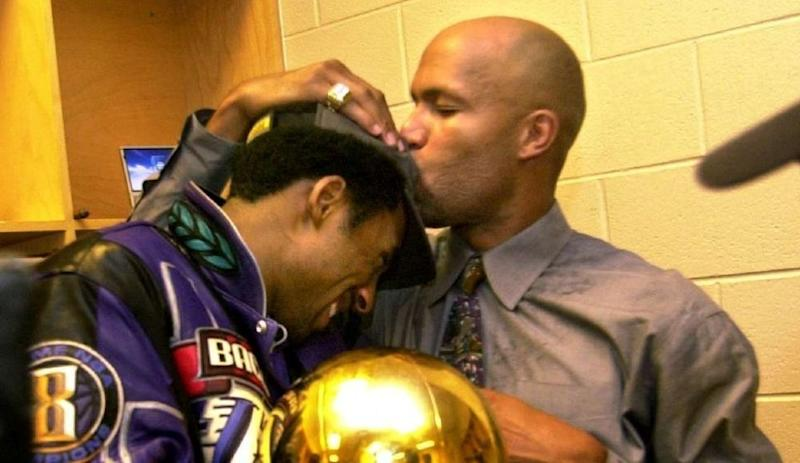Lakers' Kobe Bryant gets a kiss on the head from teammate Ron Harper after defeating the Philadelphia 76ers.