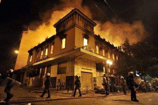Greek police walk past by a burning building in Athens during massive clashes with protestors in February 2012. No debt repayments, higher salaries and freedom from EU-IMF tutelage: Greece under the radical leftists, who are poised to win a June 17 election, seems a world removed from its current recession nightmare