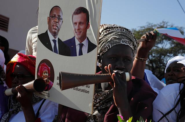 Supporters hold a board with pictures of Senegalese President Macky Sale and French President Emmanuel Macron prior to the inauguration of a secondary school in Dakar, Senegal, February 2, 2018. REUTERS/Philippe Wojazer