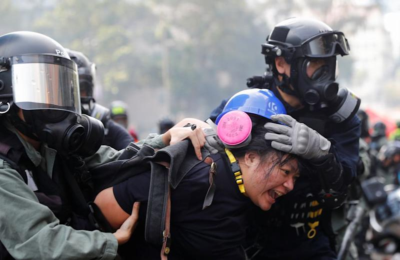 A protester is detained by riot police while attempting to leave campus