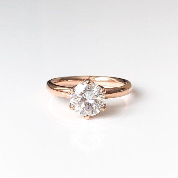 """<i><a href=""""https://www.etsy.com/listing/598669151/round-moissanite-engagement-ring-forever?ref=shop_home_active_11"""" target=""""_blank"""">Buy it fromTrudyGems on Etsy</a> for$1,500.</i>"""