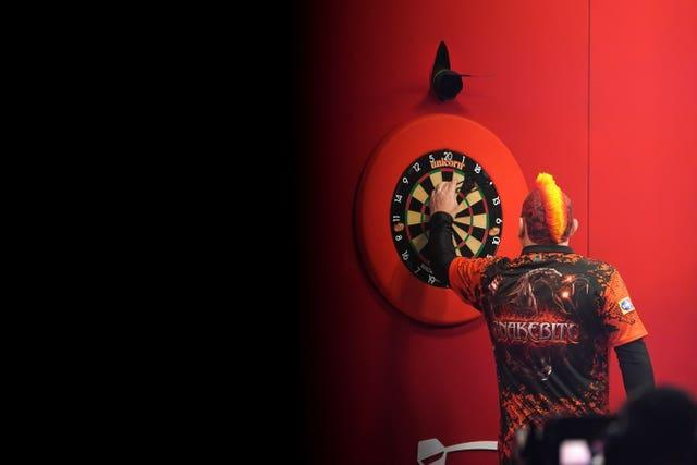Peter Wright collects his darts during his semi-final defeat to Jonny Clayton at the Ladbrokes Masters in Milton Keynes
