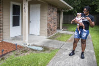 Tyesha Young, who lost her hospital job during the pandemic, holds her baby Jalayah Johnson outside their home in Waggaman, La., Friday, July 2, 2021. More than $7,000 behind on rent, Young had hoped a program in Louisiana would bail her out and allow her family to avert eviction in the coming weeks. But the 29-year-old mother of two from Jefferson Parish is still waiting to hear whether any of the $308 million available from the state for rental assistance and utility payments will give her a lifeline. She applied for money last year but never heard anything. (AP Photo/Sophia Germer)