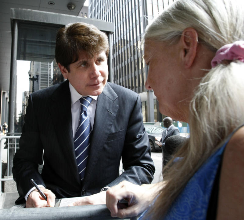 Former Illinois Gov. Rod Blagojevich signs an autograph as he departs the Federal Court building on the first day of closing arguments in his corruption trial Wednesday, June 8, 2011 in Chicago. A federal prosecutor began making final arguments Wednesday at the corruption retrial of Blagojevich, telling jurors that the ousted Illinois governor lied to their faces for seven days on the witness stand.  (AP Photo/Charles Rex Arbogast)