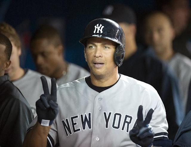 New York Yankees' Alex Rodriguez celebrates in the dugout after hitting a solo home run against the Toronto Blue Jays during the fifth inning of a baseball game in Toronto on Monday, Aug. 26, 2013. (AP Photo/The Canadian Press, Frank Gunn)