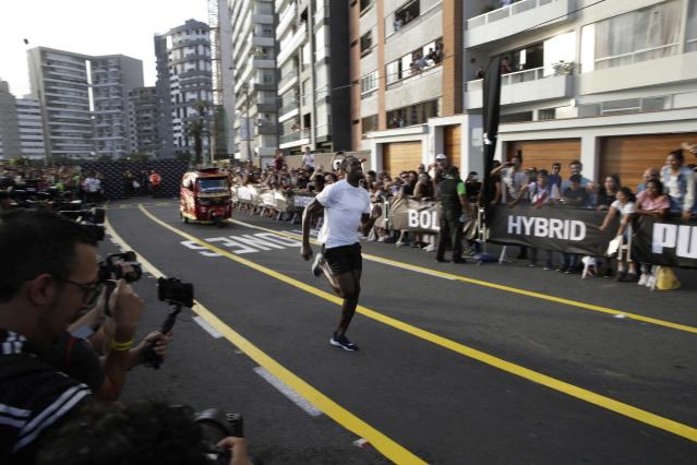 In this April 2, 2019 photo, Jamaican sprinter Usain Bolt races against a mototaxi, in Lima, Peru. Bolt, who is on a publicity campaign for Puma, went on to win the 50-meter race. (AP Photo/Martin Mejia)